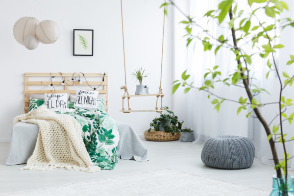 Bedroom with gray pouf, plants, double bed, lamp and swing